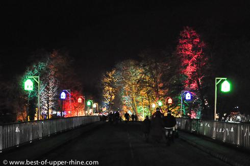 Les Sentiers de Noël s'étendent de chaque côté de la rivière ILL. Des lanternes multicolores éclairent le pont.