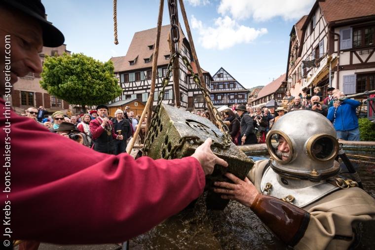 Le scaphandrier récupère les Bienheureuses, bouteilles du vin de la Confrérie qui ont passé un an dans les profondeurs de la fontaine de l'Ours à Dambach-la-Ville.